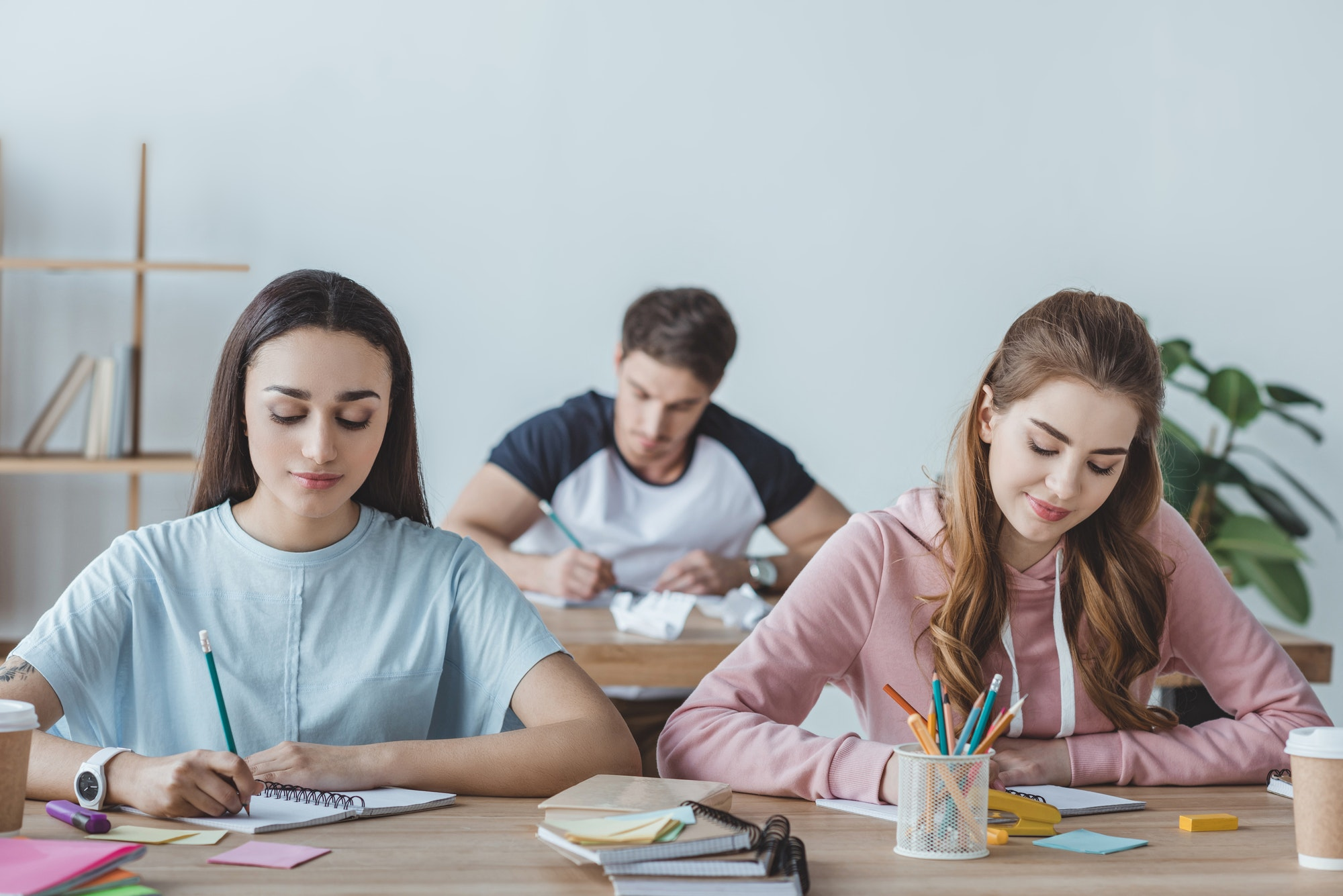 young students sitting at tables and writing exam together